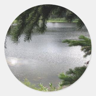 Lago de plata enmarcado por las ramas pegatina redonda