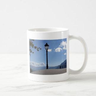 Lámpara de calle del vintage contra el cielo azul taza básica blanca
