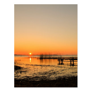 Landing stage on a lake with sunset postcard