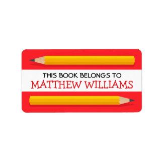 Lápices amarillos en el libro de escuela rojo del etiquetas de dirección
