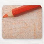 Lápiz anaranjado del color con el colorante tapete de ratones