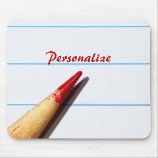 Lápiz rojo del profesor en el papel alineado con n alfombrilla de raton