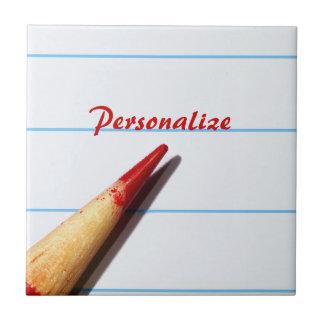 Lápiz rojo del profesor en el papel alineado con n azulejo cuadrado pequeño
