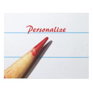 Lápiz rojo del profesor en el papel alineado con n bloc