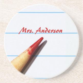 Lápiz rojo del profesor en el papel alineado con n posavasos manualidades