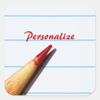 Lápiz rojo del profesor en el papel alineado con pegatina cuadrada