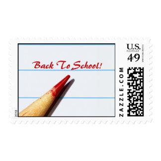 Lápiz rojo del profesor en el papel alineado de timbre postal