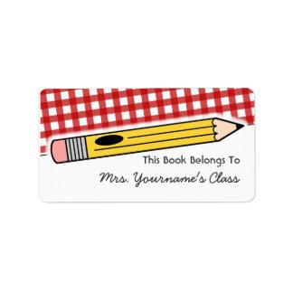 Lápiz y etiqueta roja del libro de escuela de la etiqueta de dirección
