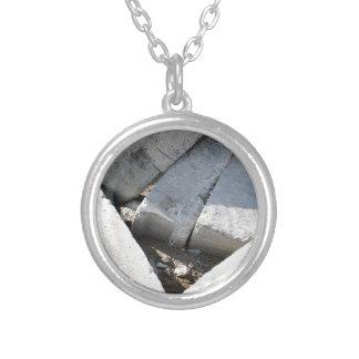 Large concrete building blocks closeup round pendant necklace