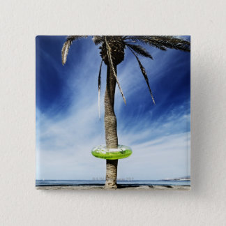 Large palm tree on a sandy beach with inflatable button