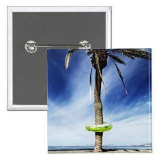 Large palm tree on a sandy beach with inflatable buttons