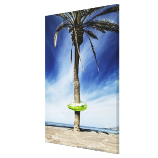 Large palm tree on a sandy beach with inflatable canvas print