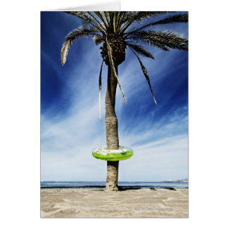 Large palm tree on a sandy beach with inflatable card