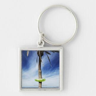 Large palm tree on a sandy beach with inflatable keychain