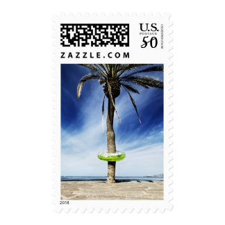 Large palm tree on a sandy beach with inflatable postage