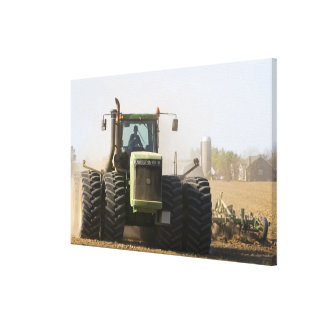 Large tractor cultivating spring soil on a canvas print
