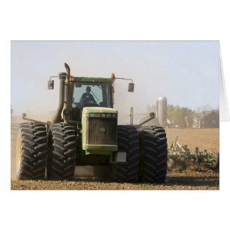 Large tractor cultivating spring soil on a card
