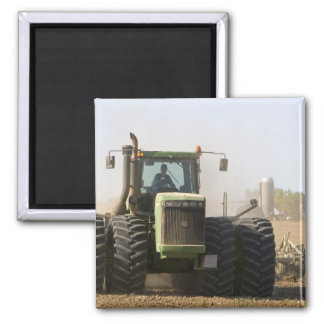 Large tractor cultivating spring soil on a magnet