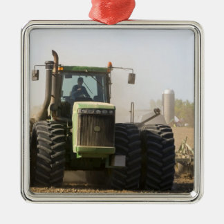 Large tractor cultivating spring soil on a metal ornament