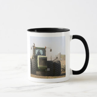 Large tractor cultivating spring soil on a mug