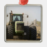 Large tractor cultivating spring soil on a christmas tree ornament
