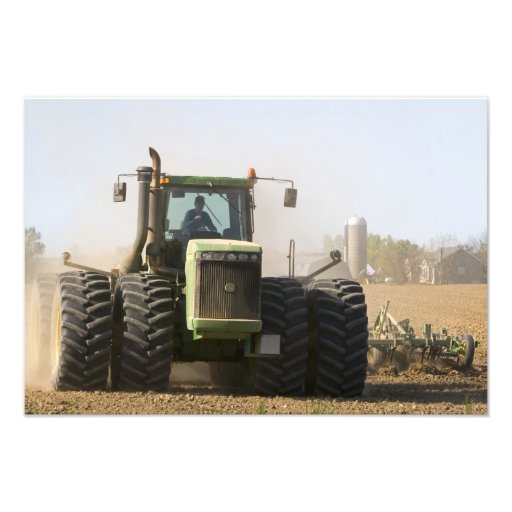 Large tractor cultivating spring soil on a photo print