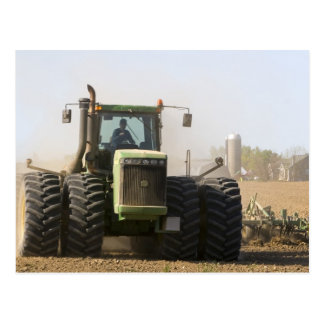 Large tractor cultivating spring soil on a postcard
