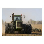 Large tractor cultivating spring soil on a posters