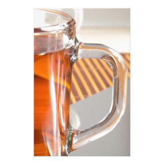 Large transparent glass mug with tea close up stationery