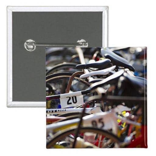 Las bicicletas en el estante en un triathlon compi pin cuadrada 5 cm