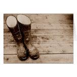 Las botas de goma fangosas de un granjero tarjeta