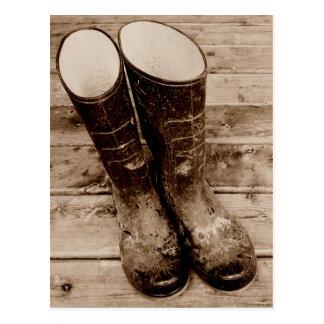 Las botas de goma fangosas de un granjero tarjeta postal