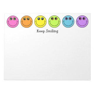 Las caras sonrientes guardan el sonreír bloc de notas