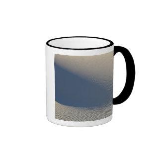Las dunas de arena en el blanco enarenan el taza de dos colores
