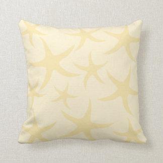 Las estrellas de mar modelan en amarillo en cojín