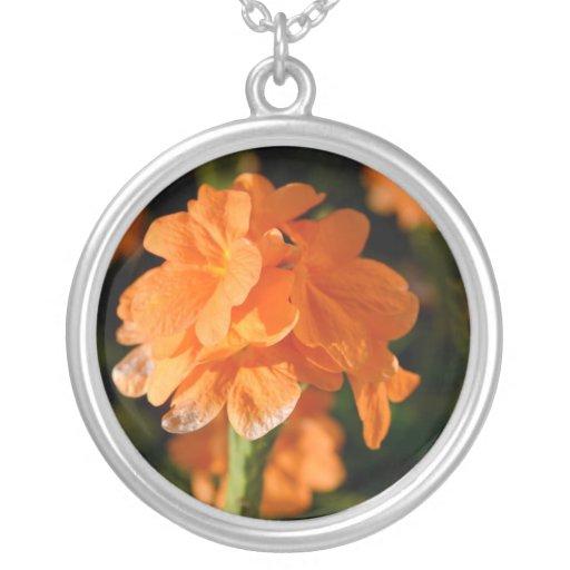 las flores anaranjadas se cierran encima de imagen colgante redondo