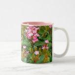 las flores rosadas, verde salen de la taza de café
