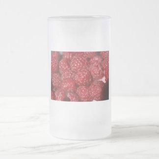 Las frambuesas rojas se cierran encima de la jarra de cerveza esmerilada