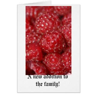 Las frambuesas rojas se cierran encima de la tarjeta de felicitación