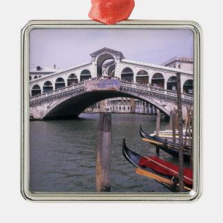 Las góndolas y los turistas acercan al puente de adorno cuadrado plateado