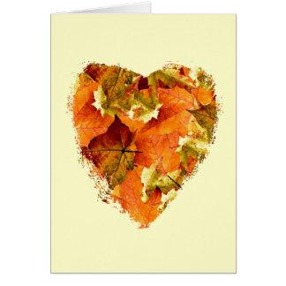 Las hojas de otoño en un corazón forman, esconden tarjeta pequeña