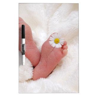 las huellas del bebé tocan con la punta del pie tableros blancos