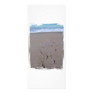 Las huellas en playa enarenan la parte posterior a tarjetas publicitarias a todo color