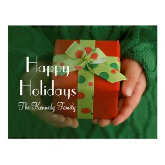 Las manos del niño que llevan a cabo un presente postales