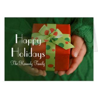 Las manos del niño que llevan a cabo un presente tarjeta de felicitación