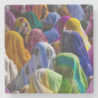 Las mujeres en saris coloridas recolectan juntas posavasos de piedra