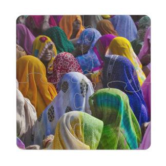 Las mujeres en saris coloridas recolectan juntas posavasos de puzzle