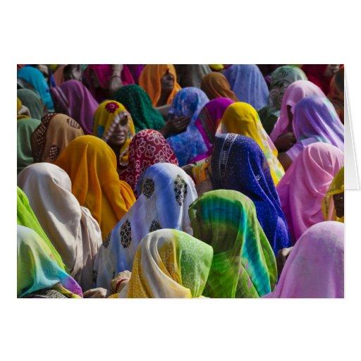 Las mujeres en saris coloridas recolectan juntas felicitacion