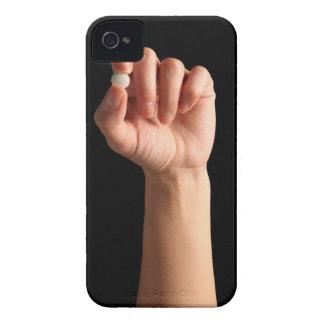 Las personas dan sostener una píldora blanca entre carcasa para iPhone 4