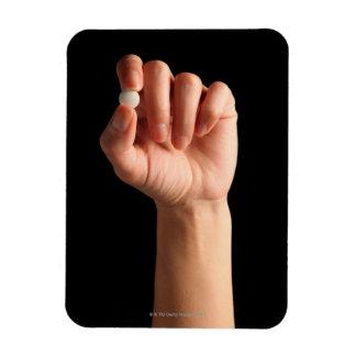 Las personas dan sostener una píldora blanca entre iman